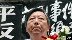 香港支聯會主席兼立法會議員李卓人捧著紅白兩色玫瑰