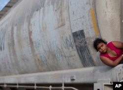FILE - A young migrant girl waits for a freight train to depart on her way to the U.S. border, in Ixtepec, Mexico, July 12, 2014.
