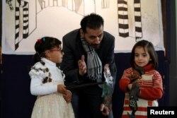 Shadi al-Hallaq, dalang wayang Suriah, bersama anak-anak saat pertunjukan untuk anak-anak difabel di Suriah, 3 Desember 2018.