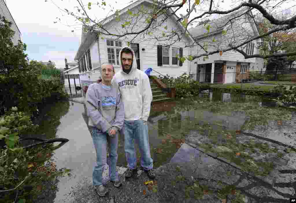 Kathy and Jeffrey Frey pose for a photograph outside their home on 7th Street which is flooded from the effects of Hurricane Sandy on Oct., 30, 2012, in Bayville, N.Y.