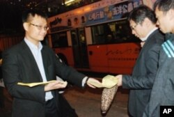 香港民主黨區議員馮煒光(左一),向居民派發活動單張