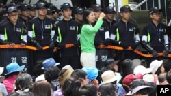 An Evangelical Baptist Church believer shouts slogans against the government as police officers stand guard in font of believers sitting by the main gate of the church in Anseong, South Korea, June 11, 2014.