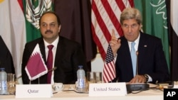 Qatari Foreign Minister Khaled Al Attiyeh, left, and U.S. Secretary of State John Kerry, right, sit alongside each other prior to a meeting with the Arab League in Paris, Monday Oct. 21, 2013. Kerry is in Paris for diplomatic talks about a peace process for Israel and Palestinian authorities. (AP Photo/Michel Euler)
