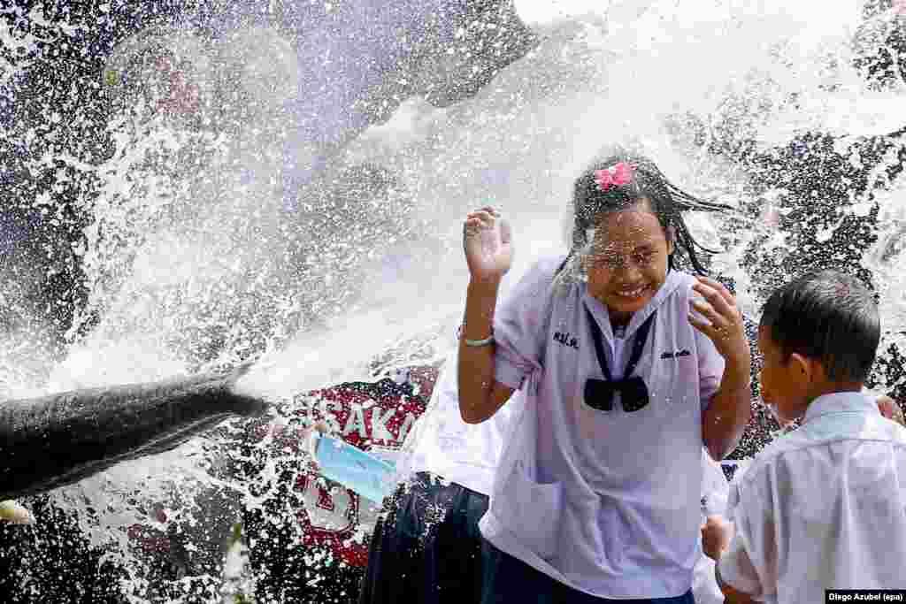 一位女学生在被列为世界文化遗产的泰国古城大城府的泼水节庆典中被大象喷洒的水淋湿。