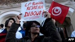 Một phụ nữ trong đoàn biểu tình cầm tấm bảng với hàng chữ bằng tiếng Pháp 'Tunisia sẽ vẫn đứng vững'