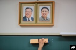 A student cleans the blackboard under the portraits of the late North Korean leaders Kim Il Sung and Kim Jong Il hanging on the classroom wall at a Tokyo Korean high school in Tokyo, Sept. 26, 2017.