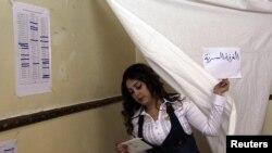 Wata mace ke fitowa bayan tayi zabe Litinin din nan a birnin Damascus