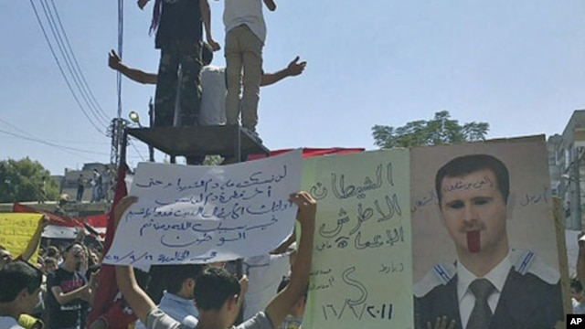 "The banners read ""The deaf and the blind devil"" (L) and ""Step down devil"" (C), as people protest against Syrian President Bashar al-Assad after Friday prayers in the city of Homs, September 16, 2011."