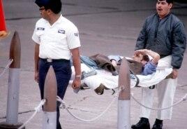 Trung sĩ Không quân James Cook, bị thương nặng sau khi máy bay của ông bị bắn hạ ở bầu trời miền Bắc Việt Nam tháng 12 năm 1972, vung tay chào kính lá cờ Mỹ từ chiếc cáng của mình trong lúc được khiêng lên máy bay (US Air Force photo)