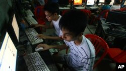 In this Sept. 27, 2012 photo, two Vietnamese students use Facebook at an internet cafe near their dormitory while they could not log in Facebook from their mobile phones because of firewall in Hanoi, Vietnam.