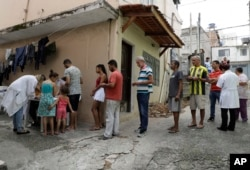 In this March 3, 2018 photo, residents stand in line to receive a free vaccine against yellow fever on the outskirts of Sao Paulo, Brazil.