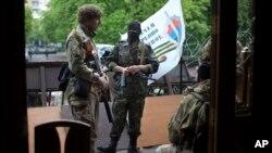 Militantes prorrusos en trajes de camuflaje montan guardia a la entrada de un edificio administrativo en Luhansk.