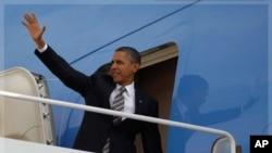 Le président Obama salue le public à la base aérienne Andrews, près de Washington, alors qu'il s'apprête à monter à bord d'Air Force One, le 24 octobre 2011