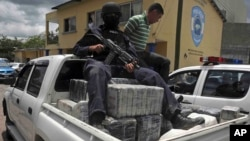 FILE - A Honduran national policeman sits on packages of cocaine that were brought to Tegucigalpa, Honduras, July 3, 2012. The cocaine was seized from a small airplane that crashed after it was being chased by planes and helicopters of the Honduran army.