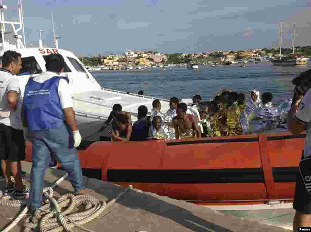 Wahamiaji waliokolewa wakiwasili na boti katika ufukwe wa Lampedusa.
