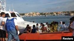 Migran yang berhasil diselamatkan dari tenggelamnya kapal di lepas pantai Italia, tiba di pelabuhan Lampedusa dengan kapal pengawal pantai (3/10).
