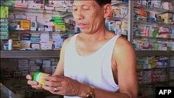 Một khách hàng Kampuchea mua thuốc chữa sốt rét tại một cửa hiệu thuốc tây ở địa phương