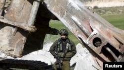 Un soldat israélien à Dura, au sud de Hebron, en Cisjordanie pendant la démolition de la maison d'un Palestinien, le 20 janvier 2016.