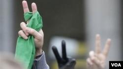 Manifestantes hacen la señal de victoria durante una demostración frente a la embajada iraní en Bruselas.