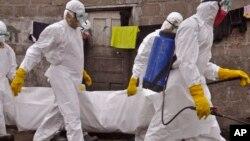 Trabajadores de la salud cargan el cuerpo de una mujer que se sospecha murió de ébola en Monrovia, la capital de Liberia.