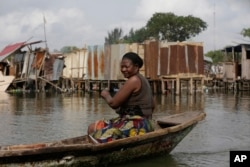 FILE - A woman paddles a canoe past residents salvaging objects from houses demolished by government officials in Otodo-Gbame waterfront in Lagos, Nigeria, March.18, 2017.