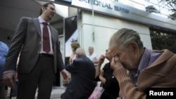 Một giám đốc ngân hàng giải thích tình hình cho những người về hưu chờ đợi bên ngoài một chi nhánh của Ngân hàng Quốc gia Hy Lạp ở Thessaloniki để nhận lương hưu, ngày 29/6/2015.
