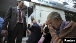 A bank manager explains the situation to pensioners waiting outside a branch of the National Bank of Greece hoping to get their pensions, in Thessaloniki, Greece.