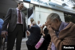 A bank manager explains the situation to pensioners waiting outside a branch of the National Bank of Greece hoping to get their pensions, in Thessaloniki, Greece, June 29, 2015.