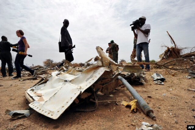 Journalists look at debris at the crash site of the Air Algerie Flight AH 5017 in Mali's Gossi region, west of Gao, July 26, 2014.