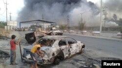 Anak-anak Irak berdiri dekat bangkai mobil yang terbakar dalam bentrokan antara pasukan keamanan dan militan Islamis terkait al-Qaida ISIL di Mosul, Irak utara (10/6).