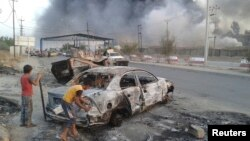 FILE - Civilian children stand next to a burnt vehicle during clashes between Iraqi security forces and ISIL.