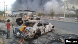 Civilian stand next to a burnt vehicle during clashes between Iraqi security forces and Islamic State in Iraq and the Levant (ISIL) in the northern Iraq city of Mosul, June 10, 2014.