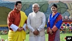 នាយករដ្ឋមន្ត្រីឥណ្ឌា Narendra Modi ឈរក្បែរព្រះមហាក្សត្រប៊ូតង់ Jigme Khesar Namgyel Wangchuck (ឆ្វេង) និងមហាក្សត្រិយានី Jetsun Pema (ស្តាំ) ក្នុងអំឡុងពិធីទទួលស្វាគមន៍នៅព្រះរាជវាំងនៅក្រុង Thimphu ប្រទេសប៊ូតង់កាលពីថ្ងៃទី១៥ ខែមិថុនា ឆ្នាំ២០១៤។