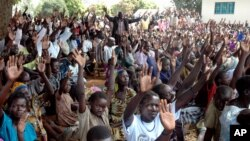 FILE - Members of the LRA community living at Koch Goma IDP camp in Gulu, Northern Uganda raise their hands after having been asked if they were ready to forgive the atrocities of the past 20 years.