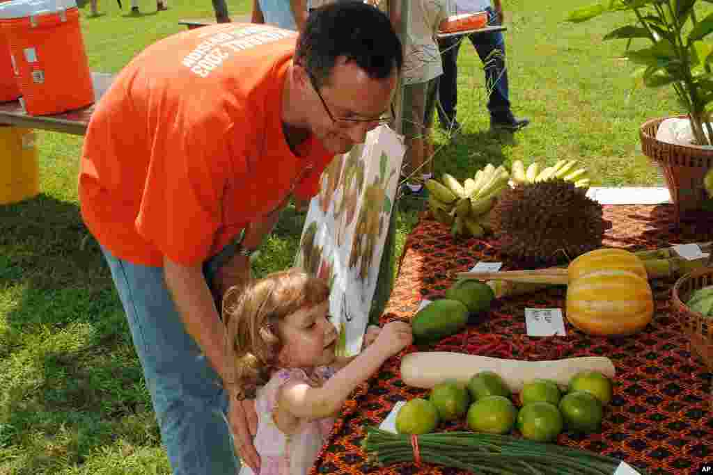 A man and his curious daughter at a display of tropical fruits and vegetables common in Cambodia.
