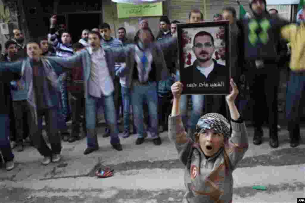 A boy holds the portrait of a man killed by the Syrian Army during a demonstration against Syrian President Bashar Al-Assad regime in Kafar Taharim, north Syria, Friday, Feb. 24., 2012. (AP Photo/Rodrigo Abd)