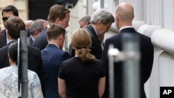 U.S. Secretary of State John Kerry, second right, arrives at Palais Coburg where closed-door nuclear talks with Iran take place in Vienna, Austria, July 8, 2015.