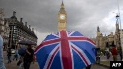 یک عابر زیر چتری با تصویر پرچم بریتانیا، جلوی ساعت «بیگ بن» بعد از اعلام نتایج رأی گیری «برگزیت» ۲۵ ژوئن ۲۰۱۶