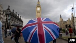 A pedestrian shelters from the rain beneath a Union Jack-themed umbrella near the Big Ben clock face and the Elizabeth Tower at the Houses of Parliament in central London, following the pro-Brexit result of the UK's EU referendum vote, June 25, 2016.