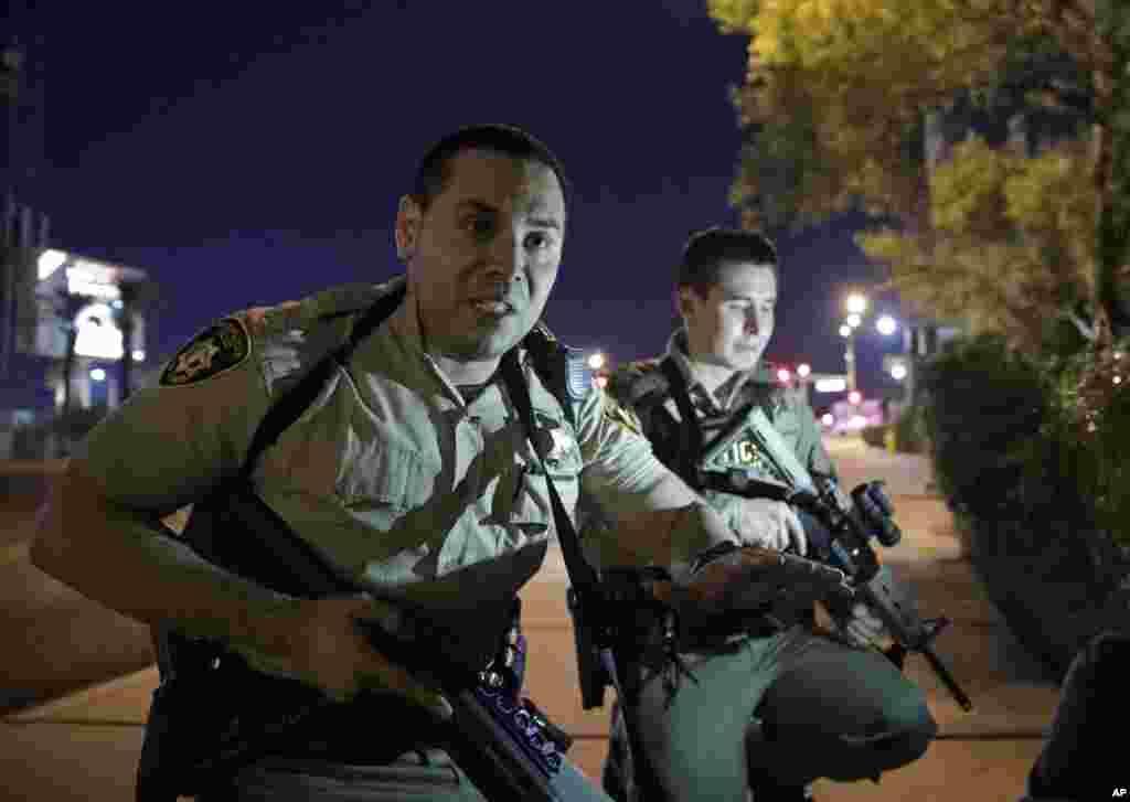 Oficial de policía recomienda a las personas protegerse en lugares cerca del hotel 'Mandalay Bay' de las Las Vegas, después del tiroteo. Oct. 1, 2017, en Las Vegas.