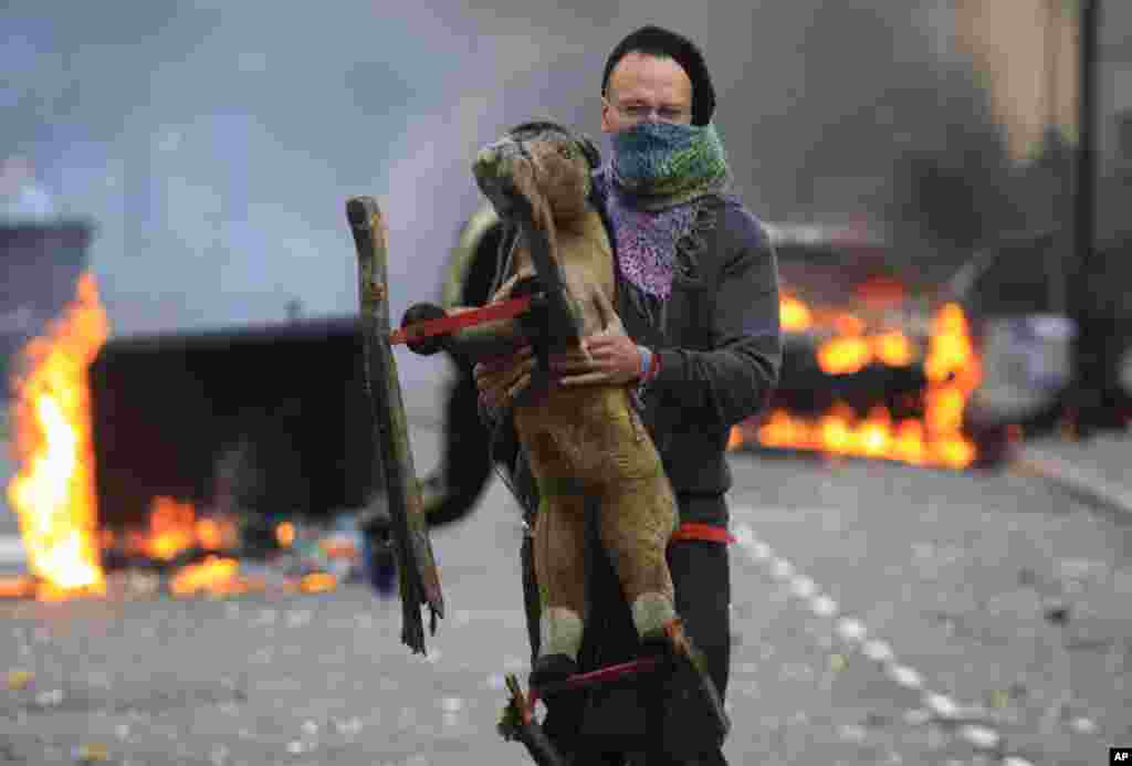 A masked man carries a toy backdropped by a burning car and garbage bins set on fire by rioters in Hackney, east London, Monday Aug. 8, 2011. Youths set fire to shops and vehicles in a host of areas of London _ which will host next summer's Olympic Game