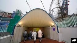Participantes en un simulacro de ataque con misil balístico de Corea del Norte en Tokio ingresan a un refugio subterráneo, el lunes, 22 de enero de 2018.