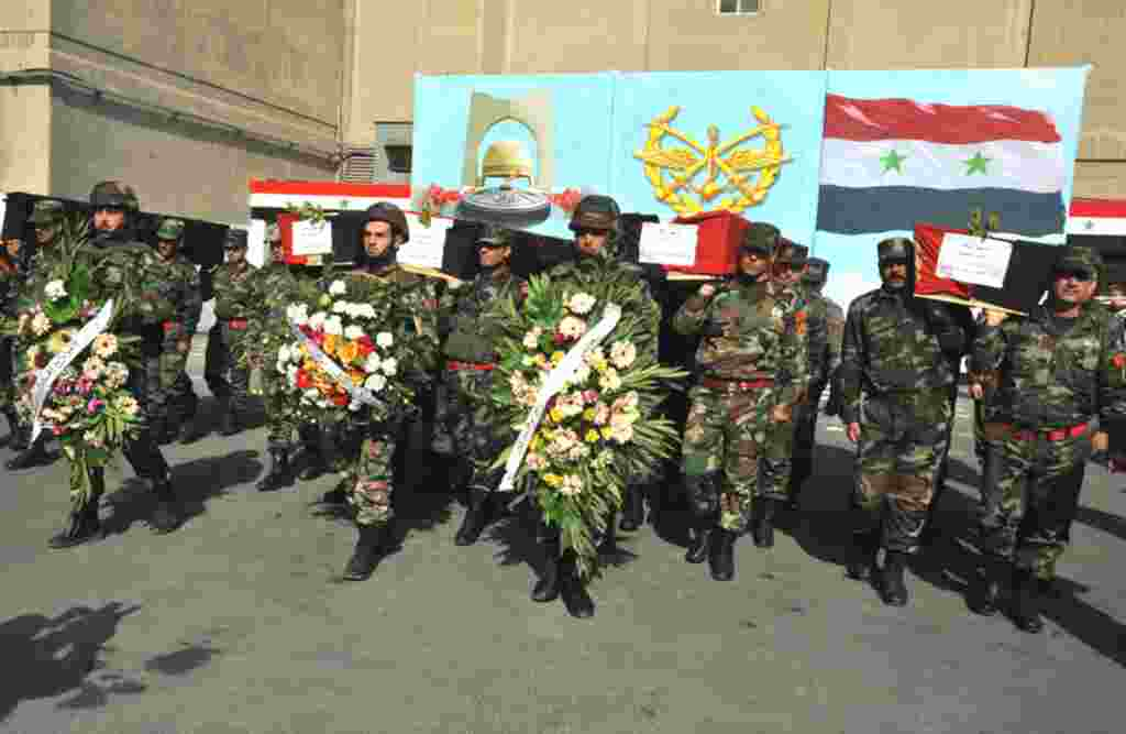 Soldados sirios marchan al funeral de sus colegas en Damasco.