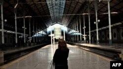 Một phụ nữ nhìn bảng thông báo về việc dịch vụ xe lửa bị gián đoạn tại một trạm xe lửa vắng vẽ ở Lisbon