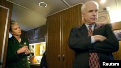 Republican presidential candidate Arizona Senator John McCain listens to advice from his campaign staff onboard his bus as his wife, Cindy, looks on near Concord, New Hampshire, Jan. 25, 2000.