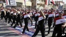 ທະຫານບ້ານທີ່ຈົງຮັກພັກດີຕໍ່ນັກບວດຕໍ່ຕ້ານສະຫະລັດ ທ່ານ Moqtada al-Sadr ເດີນຂະບວນຢຽບທຸງຊາດ ອະເມຣິກັນ ຂະນະທີ່ພວກເຂົາເຈົ້າພາກັນນຸ່ງເສື້ອທີ່ມີທຸງຊາດອີຣັກ ທີ່ຄຸ້ມ Sadr ໃນນະຄອນຫຼວງແບັກແດັດ (26 ພຶດສະພາ 2011)