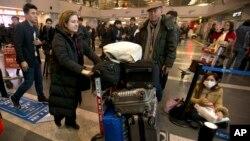 اورسلا گوتیه در فرودگاه پکن، وسایل خود را برای برای بازگشت به فرانسه حمل می کند.