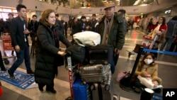 프랑스 시사주간지 '롭스'의 우르술라 고티에 기자(왼쪽 2번째)가 31일 베이징 공항을 통해 출국하고 있다.