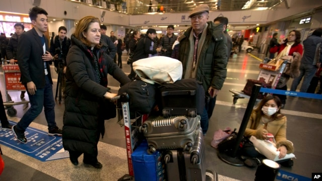 French journalist Ursula Gauthier, a reporter in China for the French news magazine L'Obs, second from left, walks through Bejing Capital International Airport in Beijing, Thursday, Dec. 31, 2015.