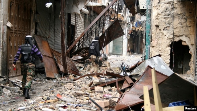 Free Syrian Army members walk through damaged buildings near the Great Mosque, or Umayyad Mosque, Aleppo, Feb. 11, 2013.